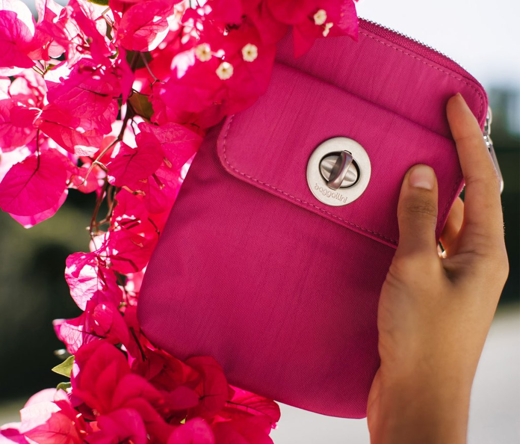 woman holding up a pink crossbody bag next to bright pink flowers
