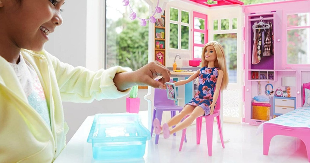 Young girl playing with a Barbie Doll and dollhouse