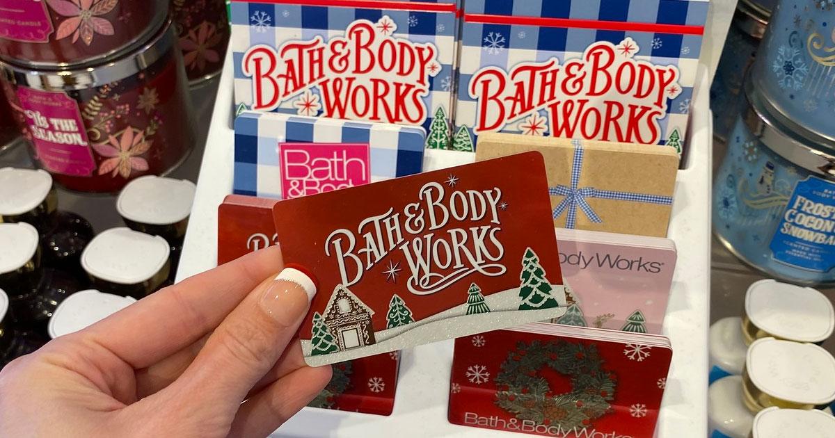 orang yang memegang kartu hadiah mandi & tubuh bertema natal merah