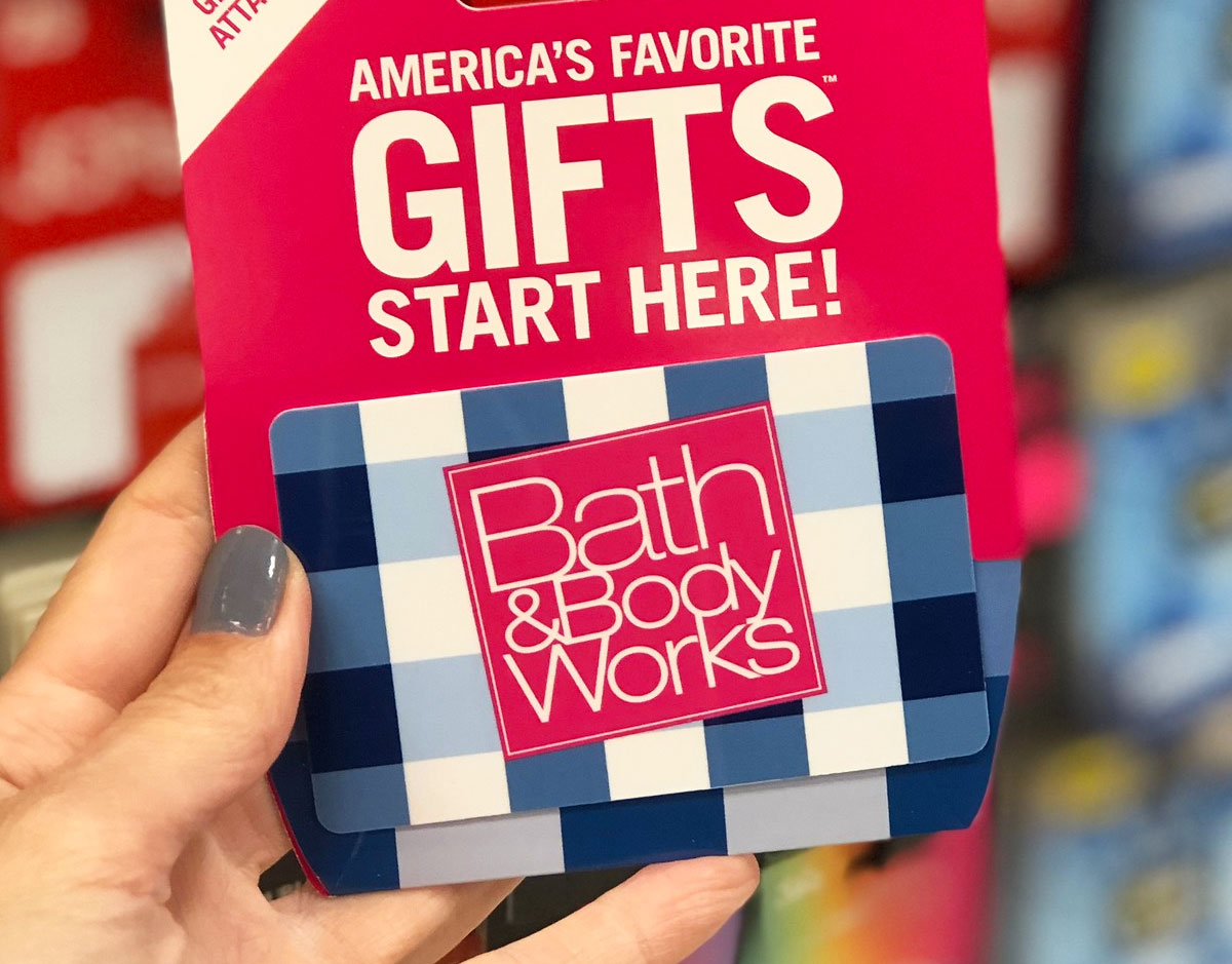 person holding up a blue and white gingham printed bath & body works gift card