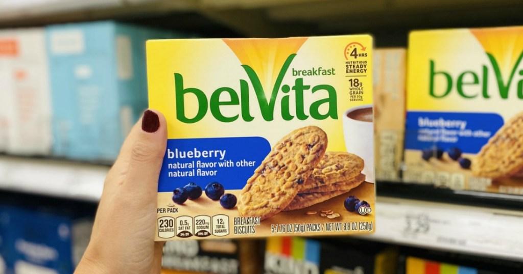 tangan wanita memegang kotak Biskuit Sarapan Blueberry Belvita