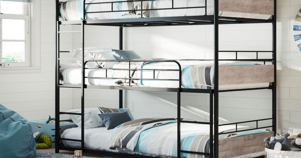 black metal bunk bed with wood panels at foot of bed assembled in a kids room