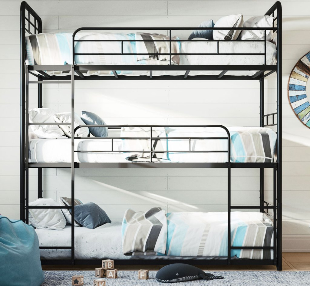 metal triple bunk bed against white wall in a kids room