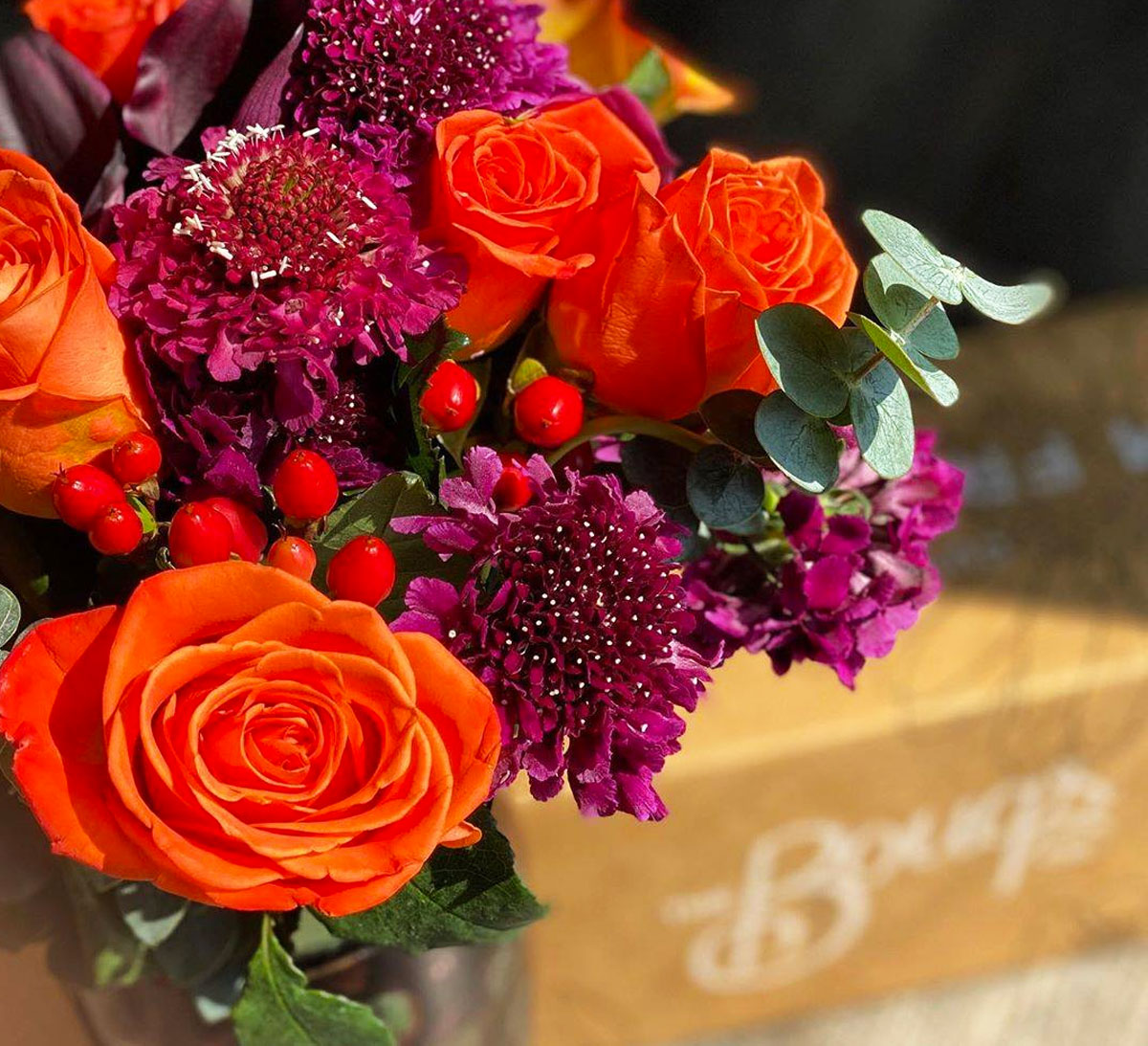 red and purple flower bouquet with bouqs box in background