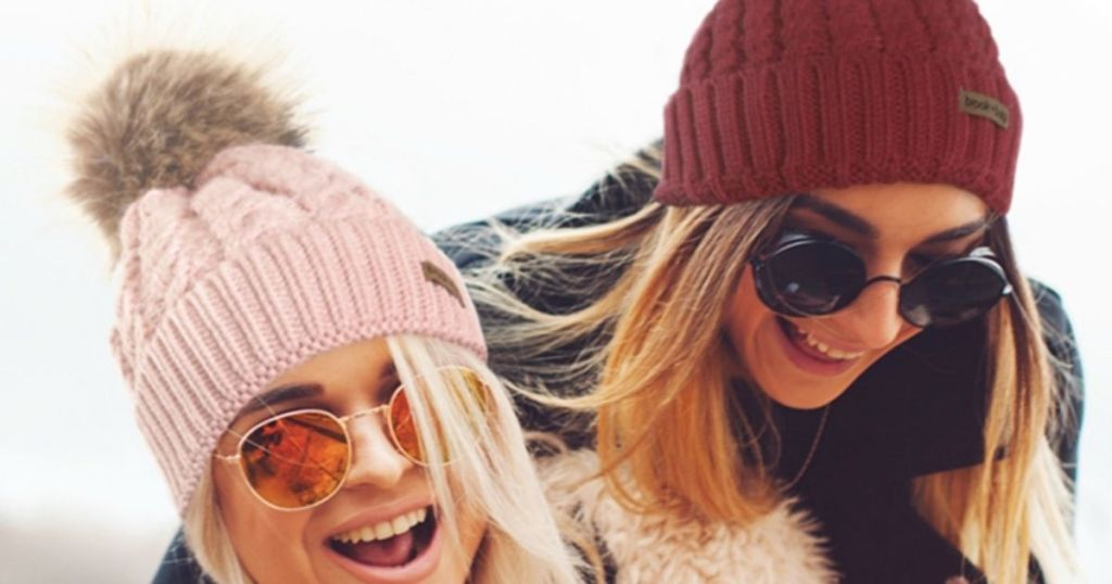 two women wearing beanies and sunglasses