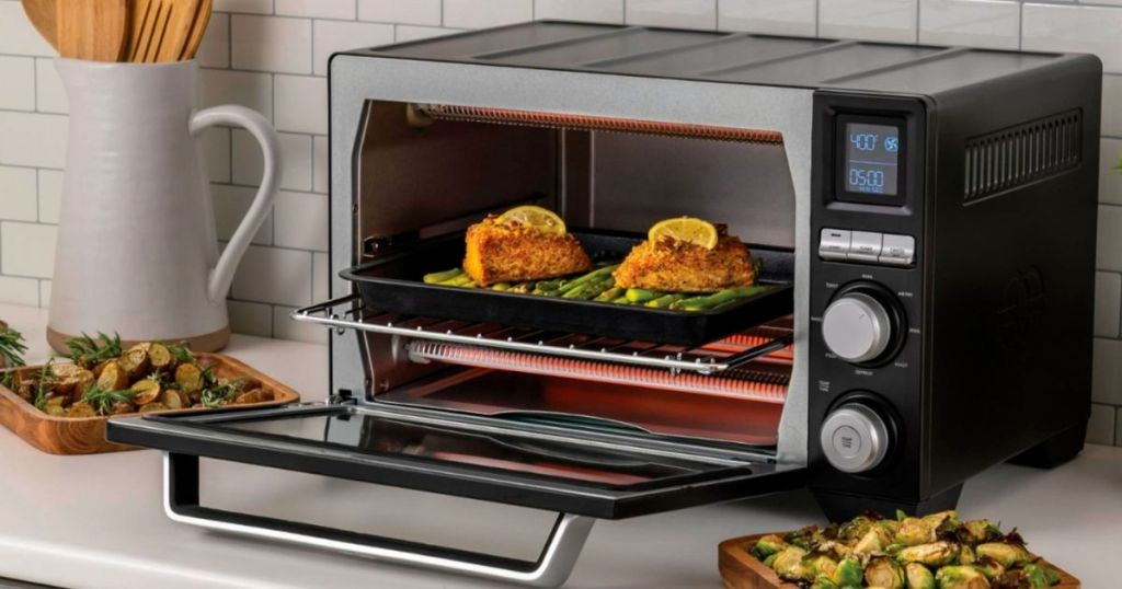Calphalon Precision Air Fry Convection Oven with door open and two pieces of chicken inside of it with vegetables in plates on the side