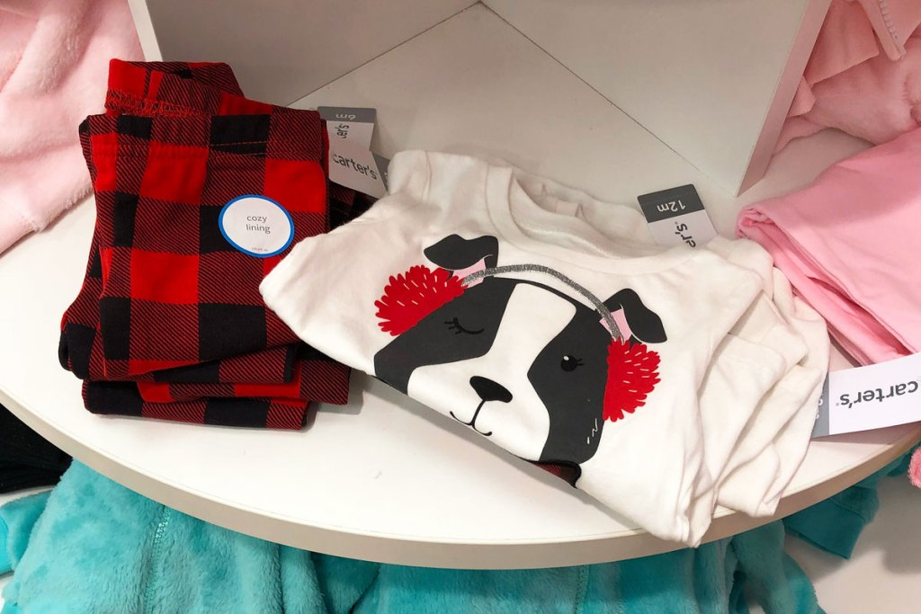 pair of red and black buffalo plaid girls leggings and white top with dog wearing earmuffs