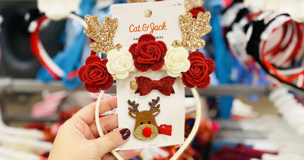 woman holding up a girls cat & jack sparkly reindeer antler headband with flowers and matching hair clips set