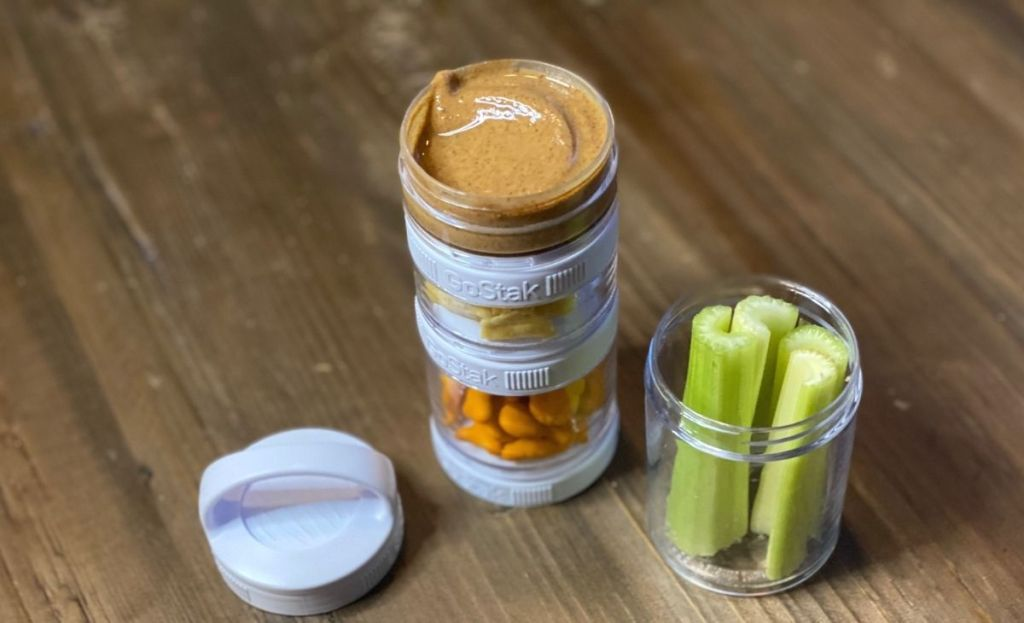 Celery and almond butter in snack containers on a table