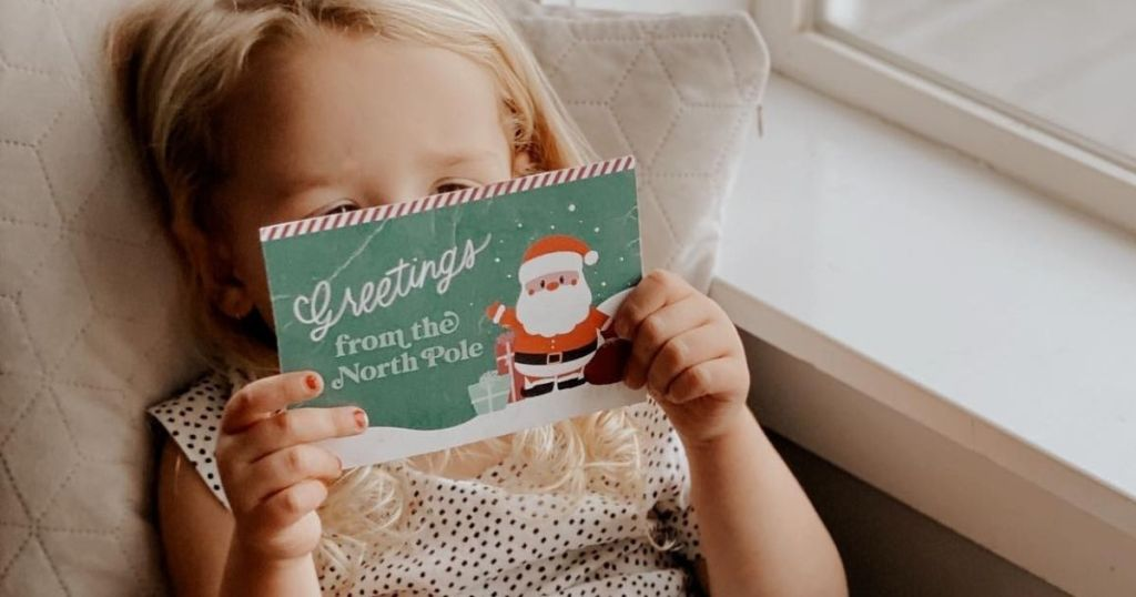 girl holding a postcard from Santa