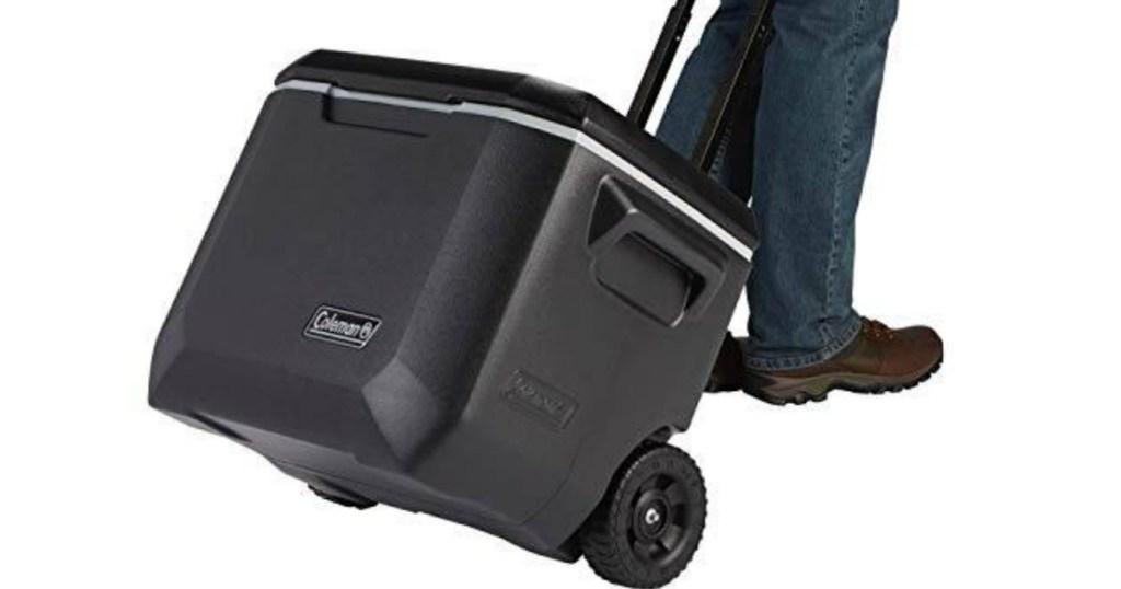 man pulling a black rolling cooler
