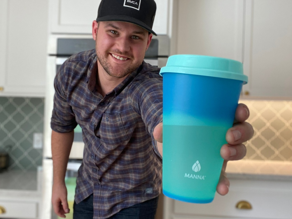 man holding a teal colored costco color changing tumbler with a lid and straw