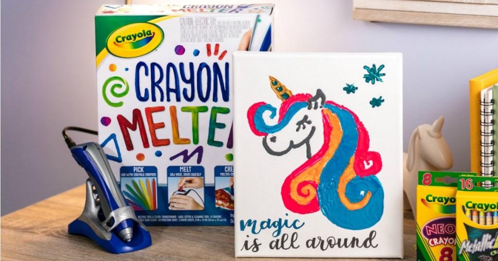 Crayola Crayon Melter shown next to artwork on desk