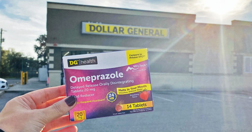 woman holding up a purple and white box of DG Health Omeprazole outside of Dollar General with sun shining over the building