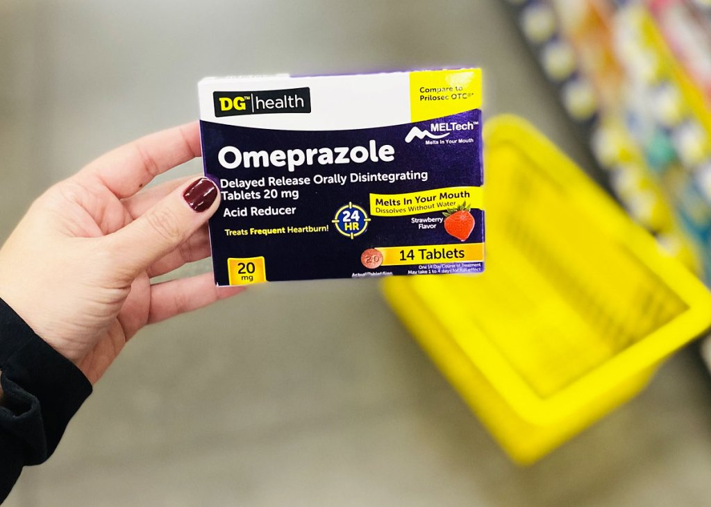woman holding up a purple and white box of DG Health Omeprazole with yellow shopping basket on ground in background