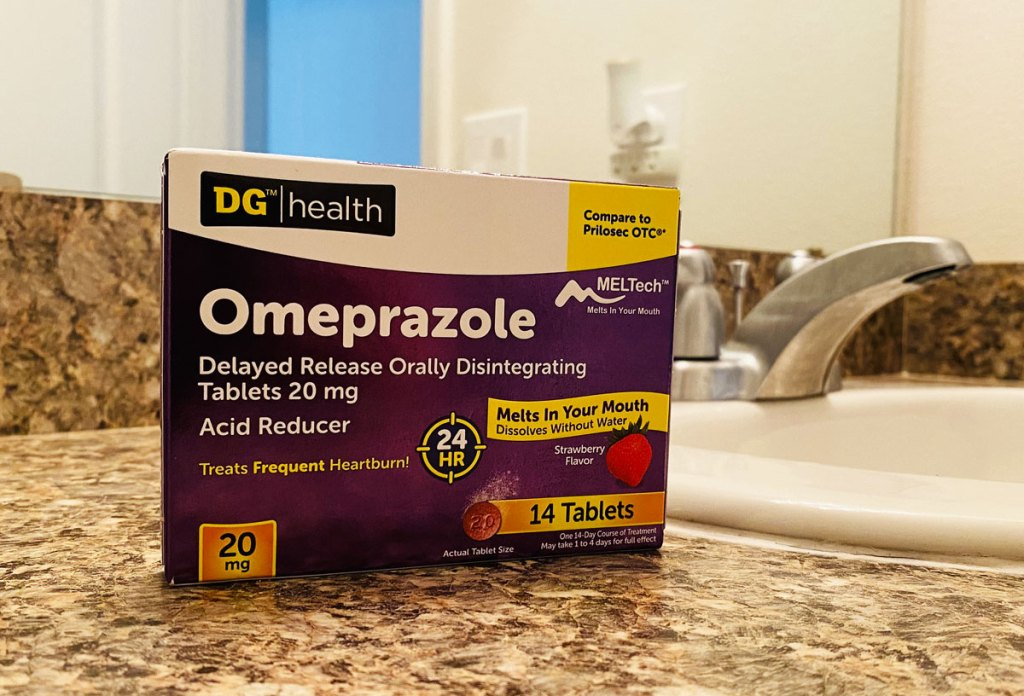 purple and white box of DG Health Omeprazole on counter in front of bathroom sink