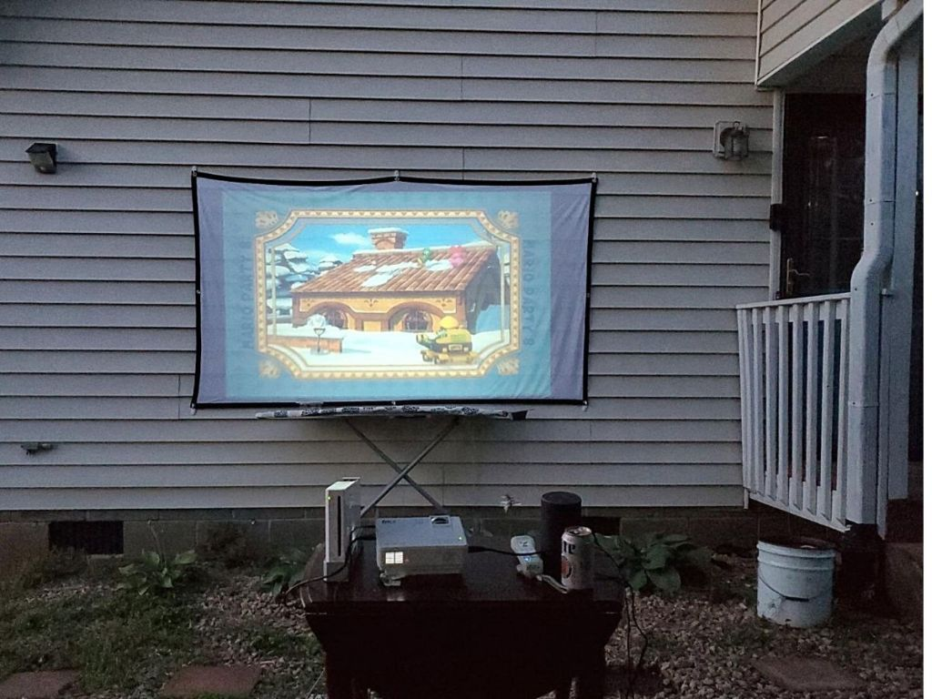 projector and screen on side of house