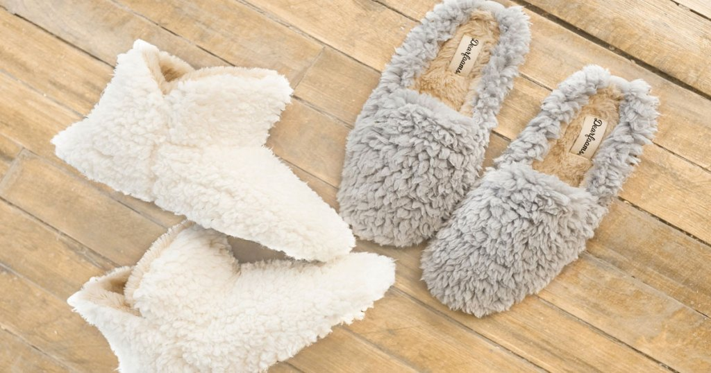 pair of white sherpa booties and grey sherpa slippers on hardwood floor
