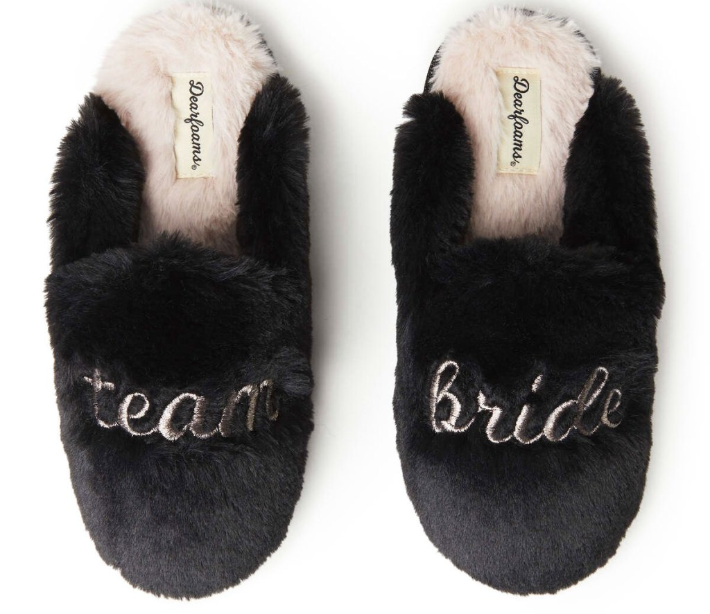 pair of black fluffy slip-on slippers that say team bride in gold