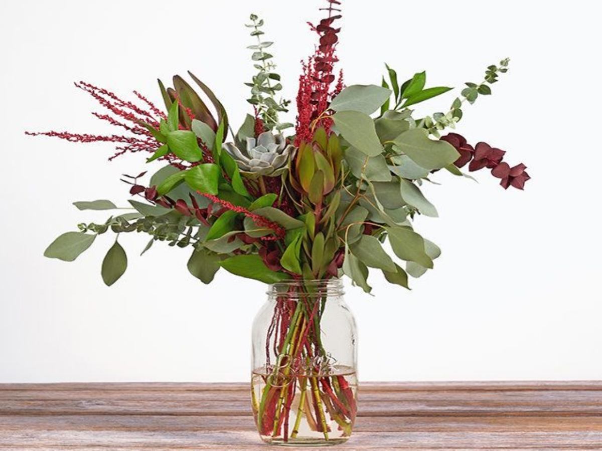 succulent bouquet in a glass mason jar on a wooden countertop