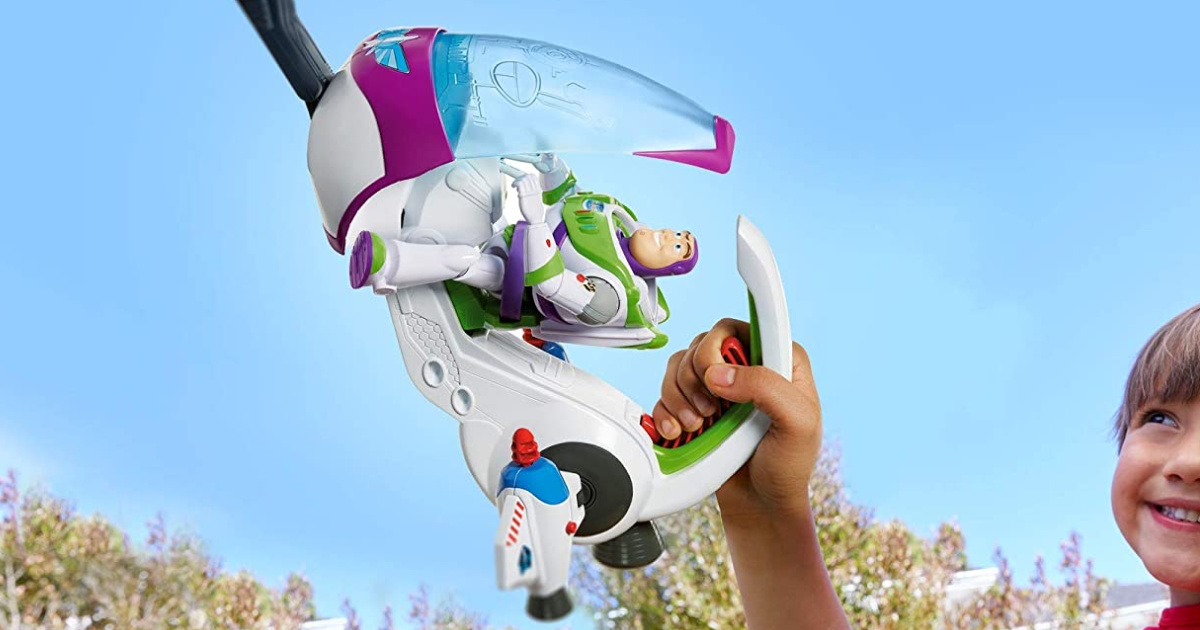 boy flying Toy Story spacecraft toy in sky