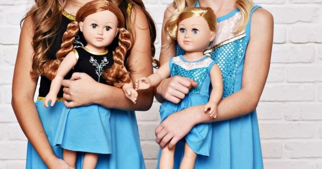 two girls holding dolls in Disney dresses