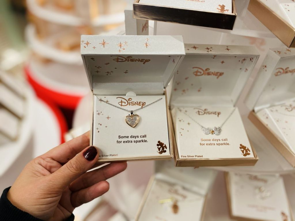 hand holding a Disney necklace in a box