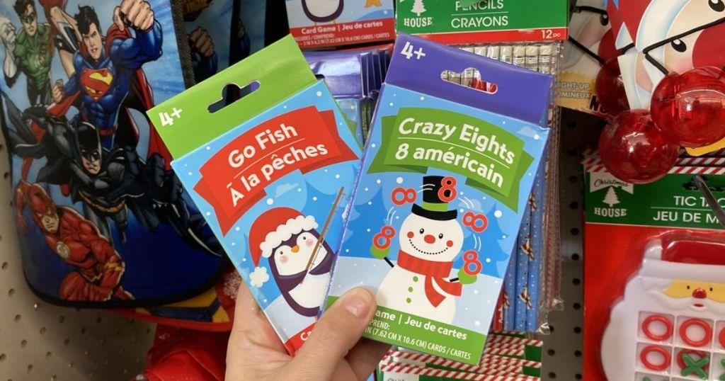 Woman holding two packs of kids Christmas theme card games