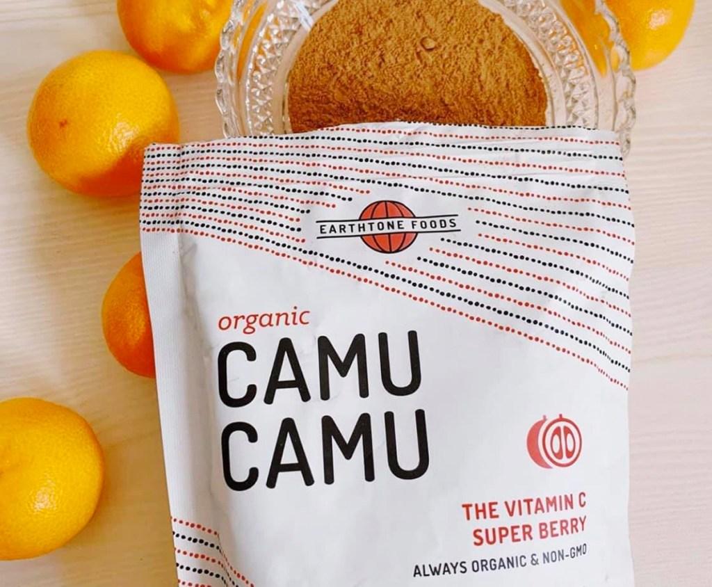 white bag of earthtone foods camu camu powder on top of glass dish of orange colored powder