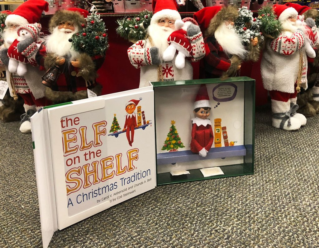 elf on the shelf boxed set on floor of store in front of santa figurines