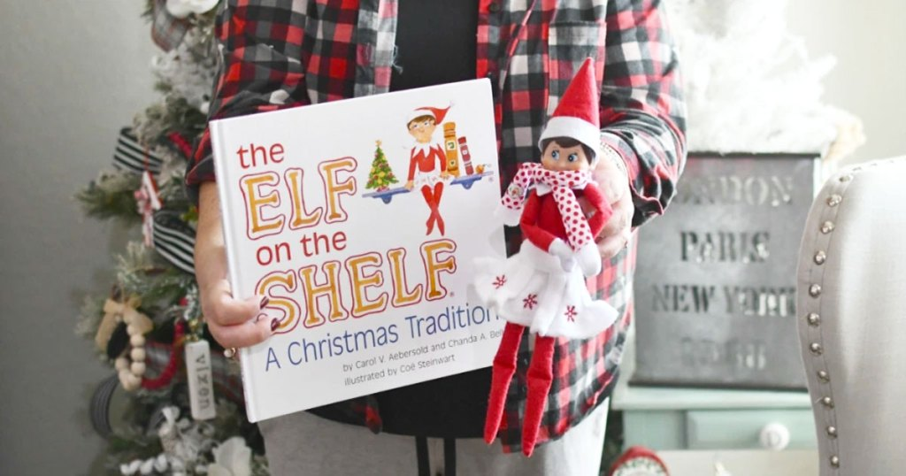 woman in red plaid shirt holding elf on the shelf book and elf in white skirt