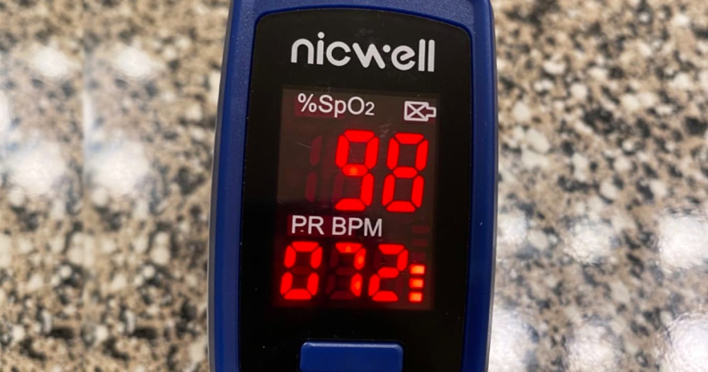 blue and black fingertip oximeter with red led screen on a granite countertop