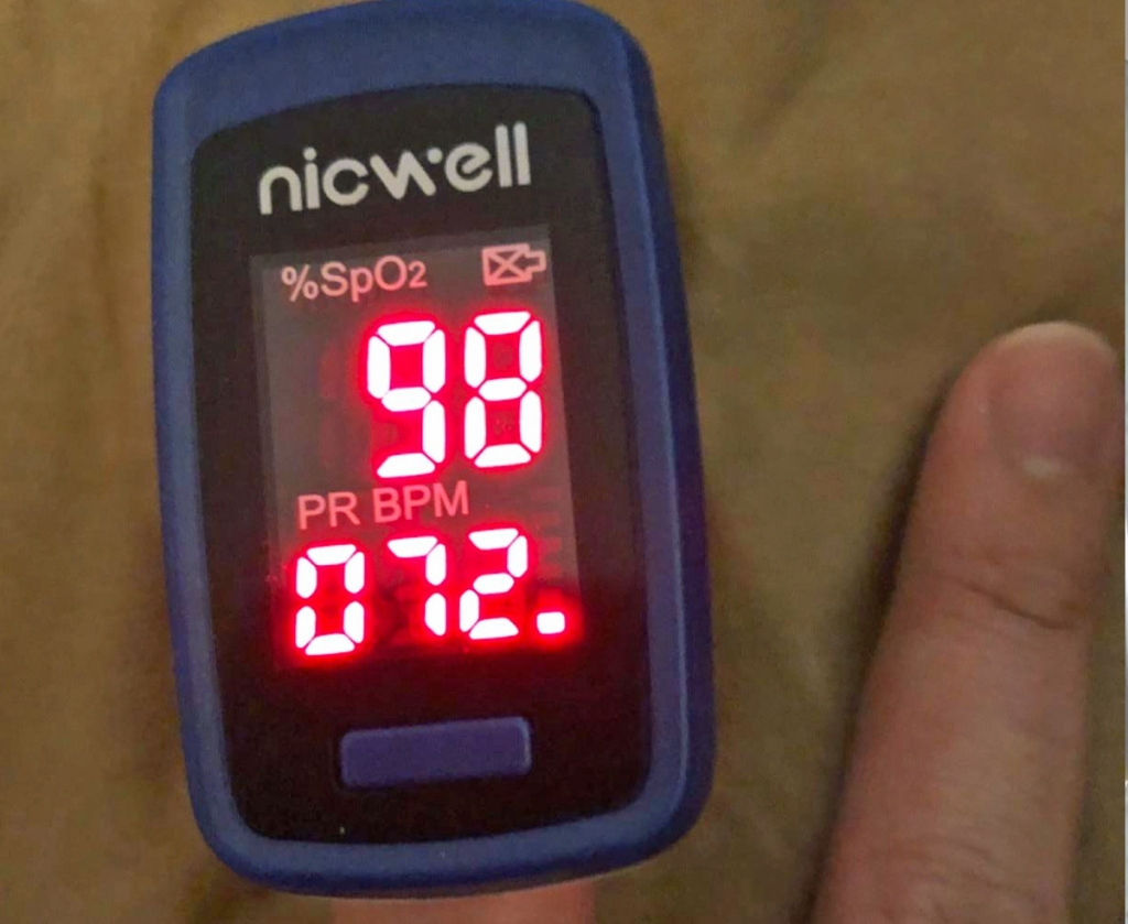 person with a blue and black fingertip oximeter on their index finger