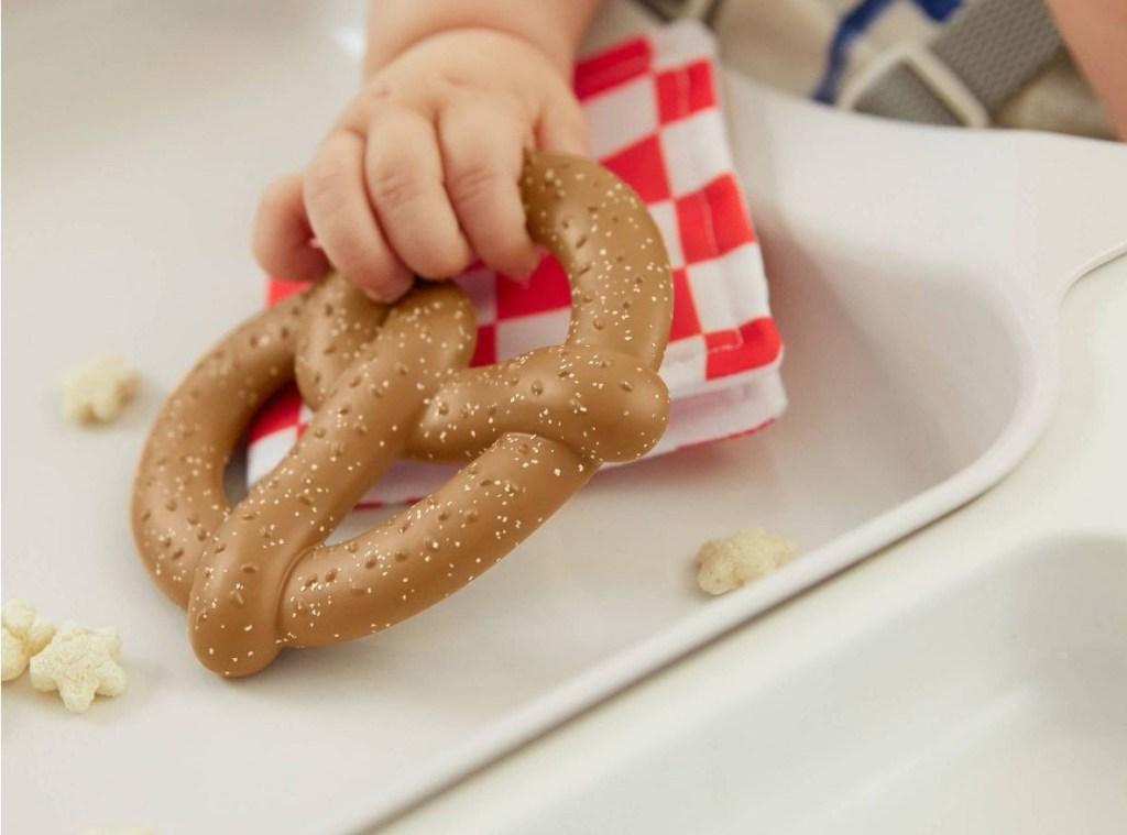 baby holding a pretzel teether