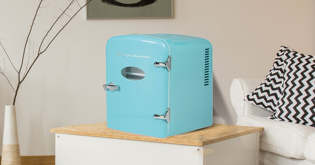 light blue mini fridge sitting on a table in a living room