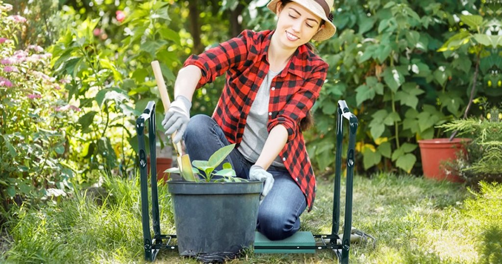woman in jeans an red and black buffalo plaid shirt kneeling on garden bench to fill up a flower pot