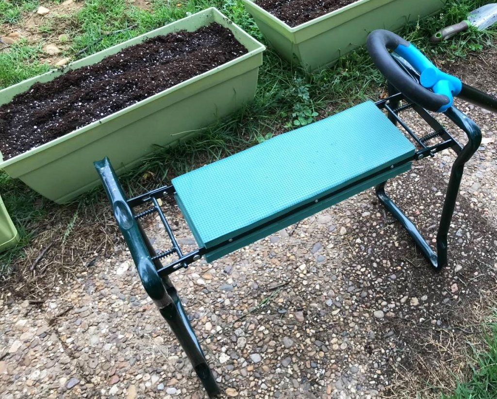 green garden bench with foam pad next to plastic planter boxes