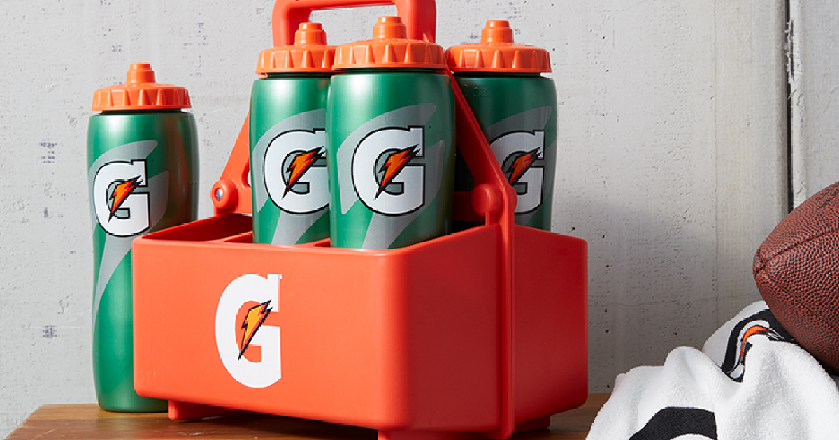 gatorade water bottles in a plastic caddy near a football and jersey