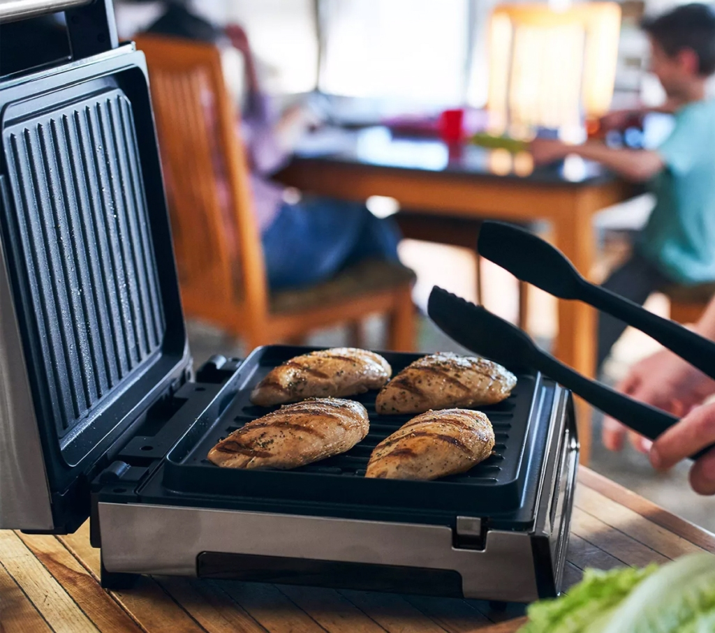 person using a square george foreman grill to grill chicken indoors