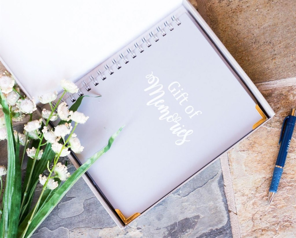 spiral bound notebook that says gift of memories with flowers and pen near it