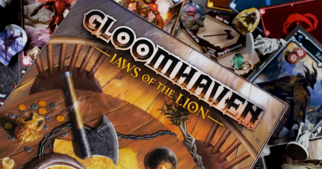 Gloomhaven: Jaws of The Lion Board Game box with game cards in background
