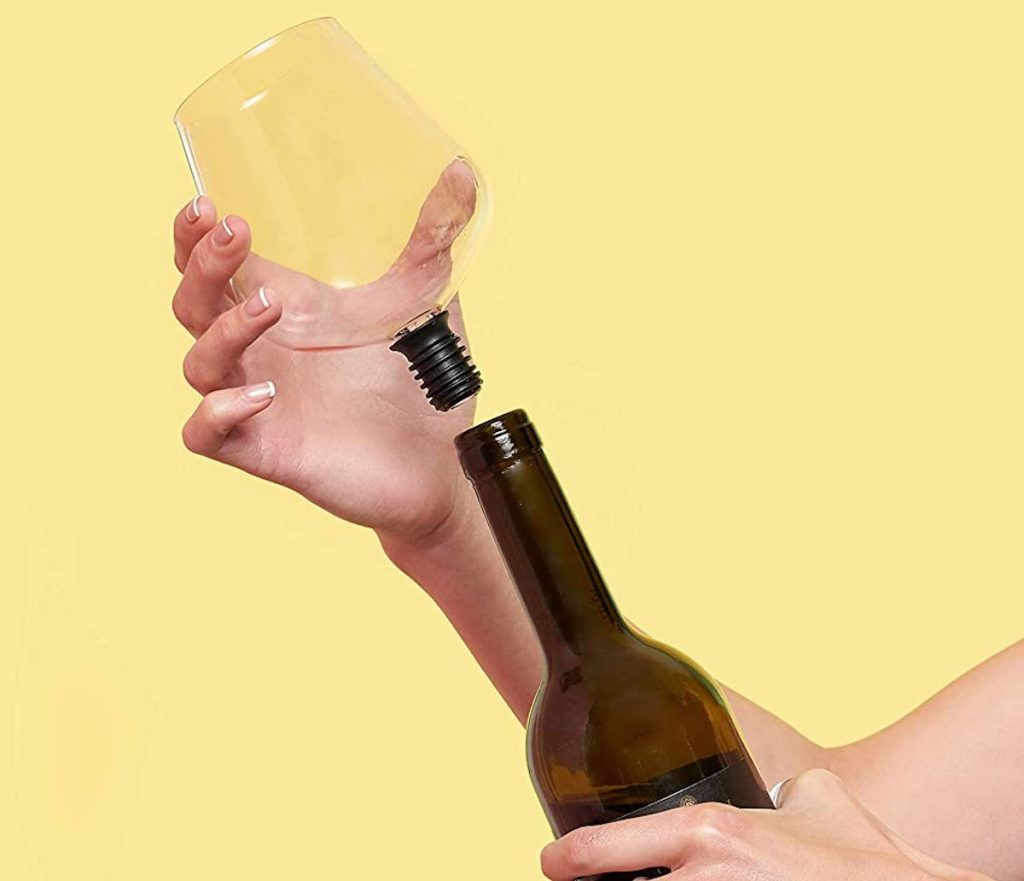 hand putting on wine glass topper on wine bottle
