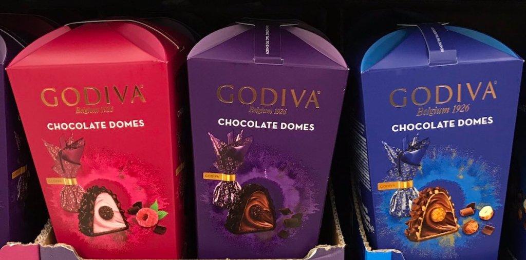 shelf with three boxes of godiva dome chocolates