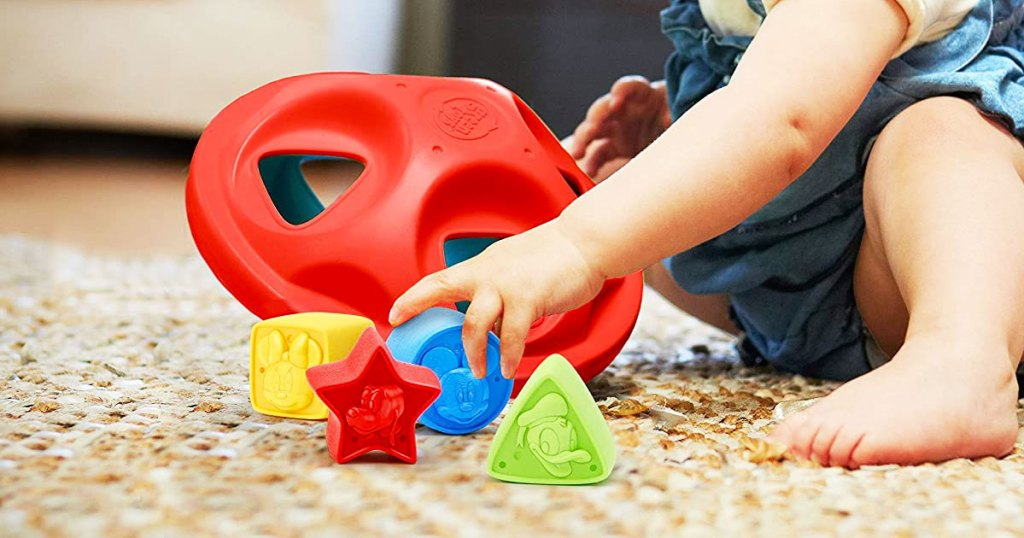 baby sitting on floor playing with large red sorting toy with disney themed shapes that fit inside of it