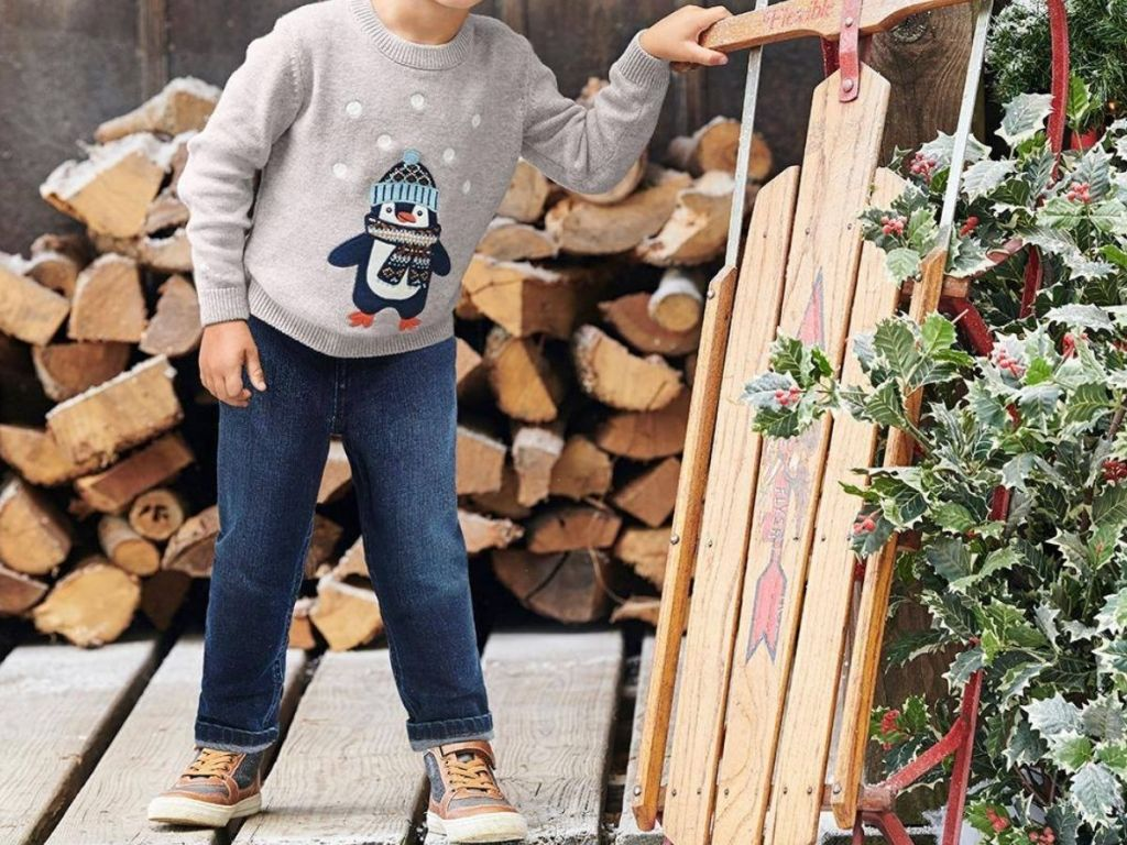 Little boy wearing Gymboree sweater and pants holding up a wooden sled