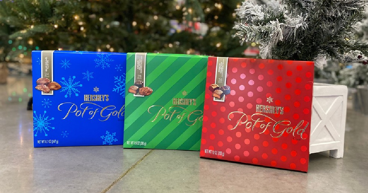 boxes of hersheys pot of gold chocolates displayed on the ground in front of a christmas tree