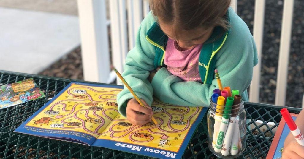 Gadis Kecil menulis di Highlights Puzzle Buzz Book