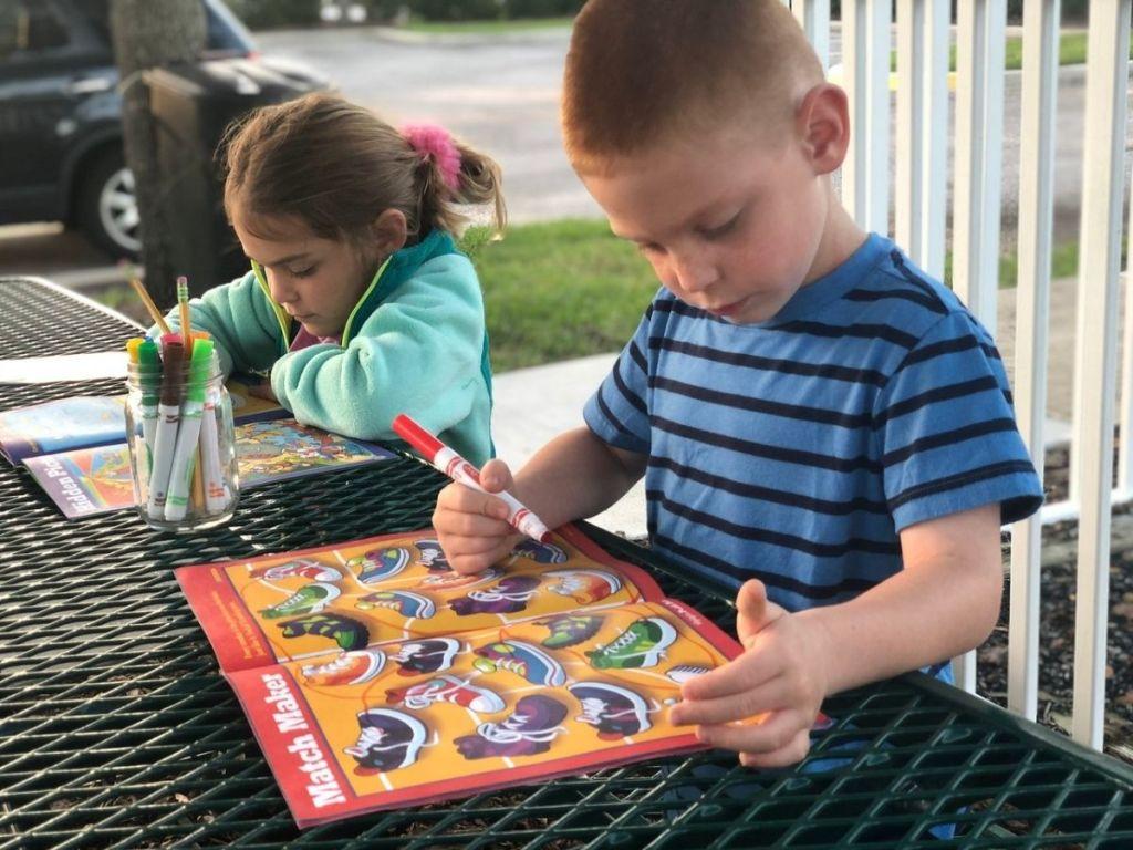 dua anak menulis di buku aktivitas di meja