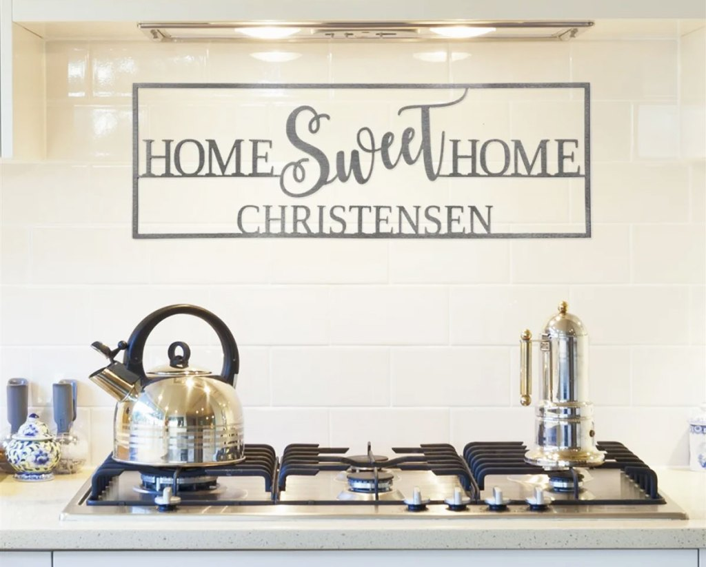 metal home sweet home sign with last name on it above a stove in kitchen