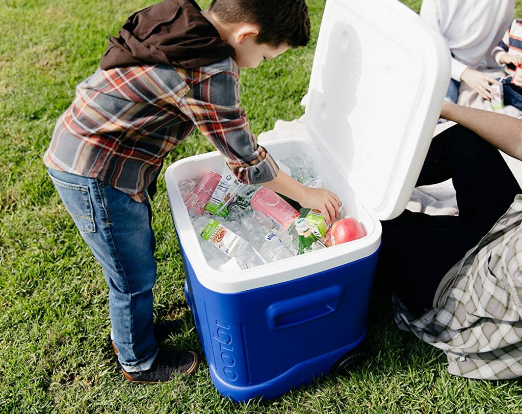 boy in hoodie and jeans bending over and reaching into a blue and white cooler filled with ice and drinks